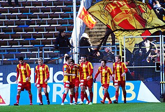 Syrianska FC - The Syrianska team, with supporters waving a flag behind them