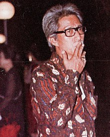Film director Teguh Karya, standing with a cigarette in his mouth