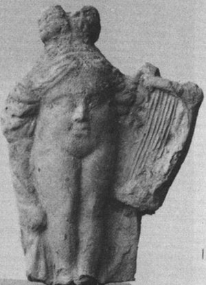 Baubo - A Greek terracotta figurine of  Baubo, of the face-in-torso type. She is holding a lyre from Priene, Anatolia.