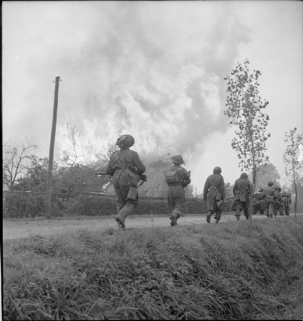 51st Highland Division infantry, supported by Daimler armoured cars of 2nd Derbyshire Yeomanry, pass a burning house in St Michielsgestel, during Operation Colin The British Army in North-west Europe 1944-45 B11218.jpg