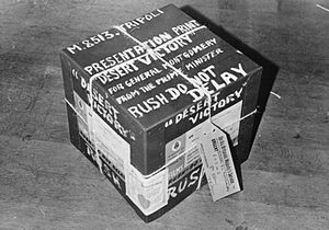 Desert Victory - A photograph of a box containing the presentation print of the film Desert Victory, which was to be sent by the Prime Minister to General Montgomery in Tripoli. The box is covered in stickers marked 'urgent'.