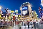 Les gens traversent l'intersection animée de Shibuya bordée de panneaux d'affichage électroniques au crépuscule