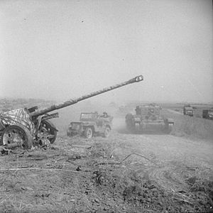 Operation Totalize - A Cromwell tank and jeep pass an abandoned German 88 mm anti-tank gun during Operation Totalize, 8 August 1944.