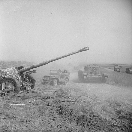A Cromwell tank and Willys MB jeep passing an abandoned German 88 mm (3.46 in) PaK 43 anti-tank gun during Totalize Totalise88gun.jpg