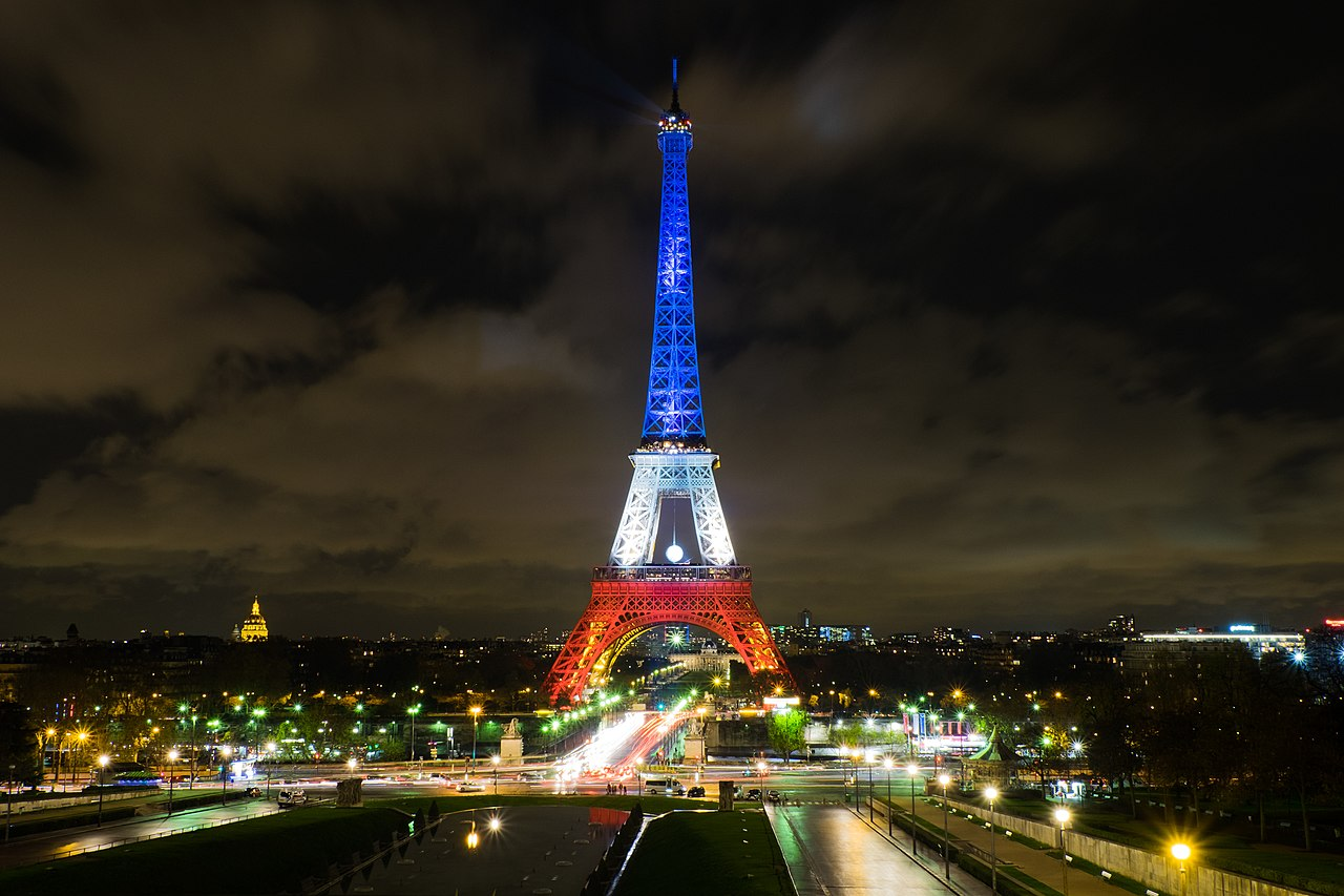 The Eiffel Tower, lit in the blue, white, and red colors of the French tricolore.