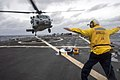 U.S. Navy Boatswain's Mate 2nd Class Joshua Husic directs an MH-60S Seahawk helicopter assigned to Helicopter Sea Combat Squadron (HSC) 9 to land aboard the guided missile destroyer USS Arleigh Burke (DDG 51) 131214-N-AP176-119.jpg