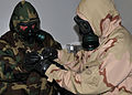 U.S. Navy Chief Explosive Ordnance Disposal Technician Jeff Rotherham demonstrates the proper collection procedure of a biological sample while wearing a nuclear, biological, chemical protective suit at a 100914-N-KZ617-003.jpg