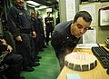U.S. Navy Engineman 1st Class Don Barron, right, blows out the candles on his birthday cake given to him as a surprise by the engineering department aboard the littoral combat ship USS Freedom (LCS 1) June 22 130622-N-JN664-015.jpg