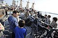 U.S. Navy Lt. Mat Rechkemmer, center, the executive officer of coastal patrol ship USS Whirlwind (PC 11), shows an MK38 Mod 2 25 mm machine gun system to Boy Scouts during a ship tour at Mina Salman Pier 120107-N-OX597-070.jpg