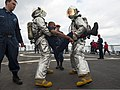 U.S. Sailors wearing firefighting proximity suits carry a simulated casualty during a damage control training drill on the flight deck of the guided missile destroyer USS Ross (DDG 71) in the Atlantic Ocean 140317-N-WX580-065.jpg