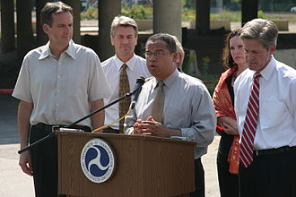 Tim Pawlenty - U.S. Representative Keith Ellison speaking at the site of the I-35W Mississippi River Bridge collapse in Minneapolis. He is flanked by Governor Pawlenty on the picture's left. To right: Mayor R. T. Rybak, Secretary of Transportation Mary Peters behind Ellison, Betty McCollum, and Senator Norm Coleman