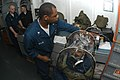 US Navy 040128-N-8955H-002 Damage Controlman 3rd Class James Allen from Oakland, Calif., conducts a MCU-2P Gas Mask fit test using a TDA 99M respirator functional testing system on Disbursing Clerk Seaman Recruit Aidan Lee.jpg