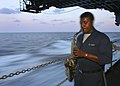 US Navy 040519-N-4911D-001 Cryptologic Technician Seaman Oscar Moore III, plays the saxophone in the ship's hangar bay during some free time.jpg