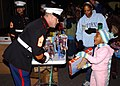 US Navy 061202-N-7427G-001 1st Sgt. John Catalinie gives out toys to a child as part of the Marine Corps Toys for Tots Program at Naval Air Station Joint Reserve Base.jpg
