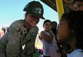 US Navy 071218-N-7367K-005 Builder 3rd Class Taylor Crow, a Seabee attached to Mobile Construction Battalion (NMCB) 1, Guam Det., shares a moment with a student at Chief Brodie Memorial Elementary School.jpg