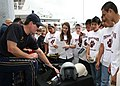 US Navy 090506-N-5366K-144 Chief Special Warfare Operator (SEAL) William Davis, assigned to the U.S. Navy Parachute Team the Leap Frogs, shows children military equipment at Dr. Pepper Ball Park after the Team parachuted into t.jpg