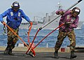 US Navy 091106-N-5538K-040 Sailors assigned to the amphibious transport dock ship USS Denver (LPD 9) remove a cargo pendant from fresh supplies during a vertical replenishment.jpg