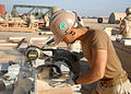 US Navy 100106-N-9564W-048 Builder Constructionman Apprentice Eric Maldonado uts wood for the construction of a Southwest Asia hut in the expansion area of Camp Leatherneck.jpg
