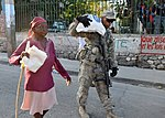 US Navy 100131-N-6214F-035 A Soldier assigned to the 82nd Airborne Division based in from Fort Bragg, N.C., helps a woman carry a 55-pound bag of rice that she received from the World Health Organization at a food distribution.jpg