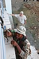 US Navy 110228-A-0566T-347 A member of the Belize Special Assignment Group climbs a ladder to secure an area as Ens. Brendon Hamm acts as a safety.jpg