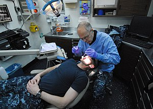 US Navy 120112-N-OS575-114 Capt. Gary Hammond, from Buffalo, N.Y., performs a dental cleaning on Lt. Jeff Doody, from Glenwood, Minn., aboard the a.jpg