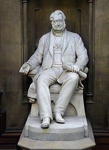 A white statue of a seated middle-aged man in mid-19th Century clothing, holding rolled plans in his left hand