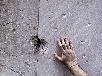 Remnants of the damage from the 1920 bombing are still visible on 23 Wall Street. Wallstreetbomb.jpg