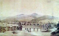 Watercolor depicting a man, dog and cart in front of a farm building, while in the background rise a series of hills on the slopes of which are forest, cattle and fields