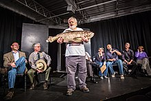 A bearded person stands, holding an enormous fish on a small, all-black stage while seven people sit on chairs behind.