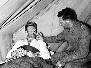 Blond man in bed having his temperature taken by another man wearing a military uniform