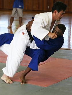 Execution of a judo throw (ōuchi-gari). The player in blue is being thrown.