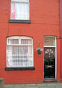 Exterior of a red brick building. Visible are a black door with a small window just above it, two larger windows to the left of the door, one above the other, and a flowerpot between the door and the lower larger window