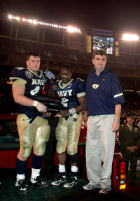 U.S. Naval Academy defensive end (DE) Jeremy Chase, left, Quarterback (QB) Lamar Owens, center, and head football coach Paul Johnson receive the Poinsettia Bowl trophy after defeating Colorado State 51-30. The college teams played in the inaugural Poinsettia Bowl at Qualcomm Stadium in San Diego, CA.