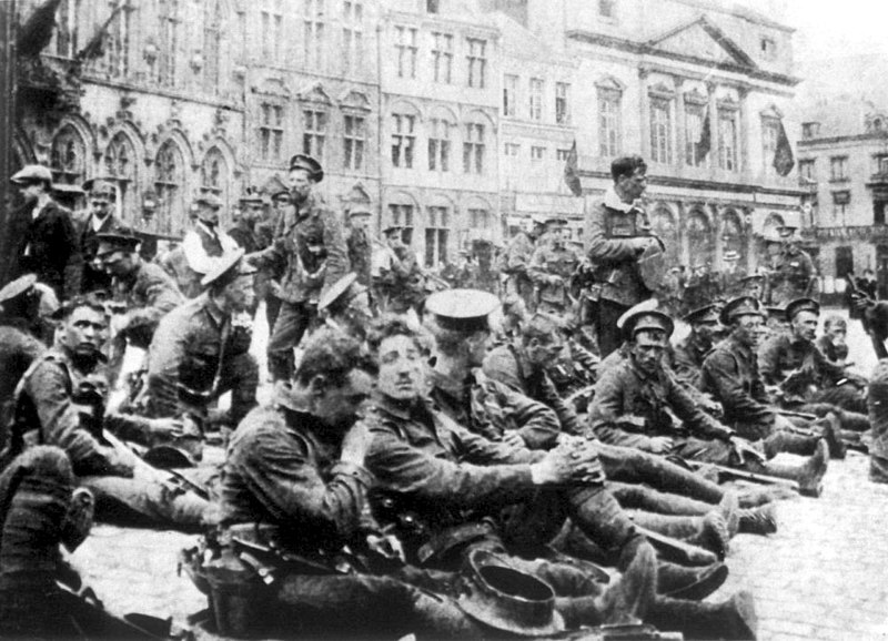In the foreground soldiers are sitting down with civilians walking behind them. In the distance are four storey buildings