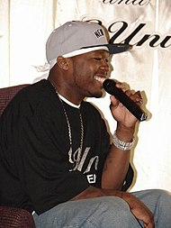 A young black man, seated, wearing a black shirt and a gray baseball cap.  He is smiling and speaking into a microphone.
