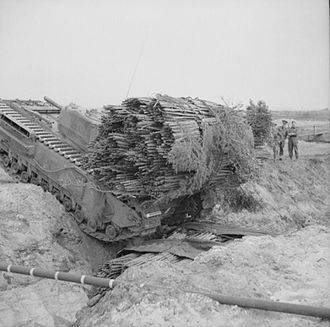 Fascine - A Churchill AVRE, carrying a fascine, crosses a ditch using an already deployed fascine, 1943.