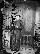 A young man standing and reading a book NLW3364690.jpg