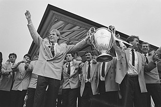 Guus Hiddink - Hiddink (right) and Hans van Breukelen (left) holding the European Cup on arrival at Eindhoven Airport