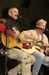 A grey-haired man with a moustache playing the guitar and singing into a microphone.  A blond-haired man, also playing a guitar, is in the background.