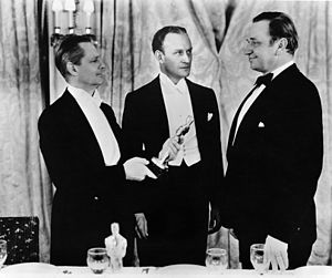 5th Academy Awards - Wallace Beery, with Lionel Barrymore and Master of Ceremonies Conrad Nagel