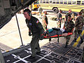 Airmen carry a patient onto an Air Force Reserve Command C-130 Hercules.jpg