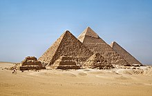 The three main Pyramids at Gizeh are shown rising from the desert sanആധുനികh three smaller pyramids in front of them