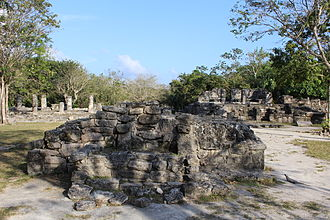"""San Gervasio (Maya site) - """"The Altar"""" on the central plaza. In the background, one can see Las Columnas (""""the Columns"""") on the left, and Los Nichos (""""the Niches"""") on the right. In the front right, an iguana is facing the structure."""