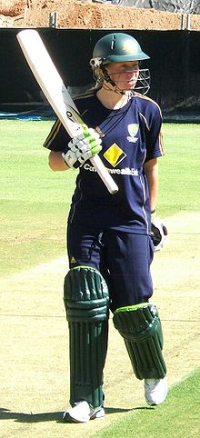 Young woman with a short blonde ponytail wearing a dark blue T-shirt, baseball cap and trackpants with gold stripes. Advertising logos of Adidas and Commonwealth Bank are present on the clothes. She is wearing a green helmet with a grill and pads on her legs, gloves and is holding a bat in her right hand.
