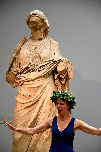 Laurel wreath - An actress performing a play. She wears a laurel wreath and stands in front of a statue of a woman from the Mausoleum at Halicarnassus. Room 21, The British Museum, London