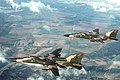 An air-to-air top left view of two 494th Tactical Fighter Squadron, 48th Tactical Fighter Wing F-111F aircraft loaded with Mark 82 high-drag bombs. The 494th TFS has been deployed t - DPLA - 0574dd0a5370212535980d0be0951b92.jpeg