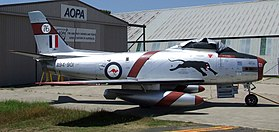 Sabre single-engined jet fighter painted silver and parked in front of a hangar