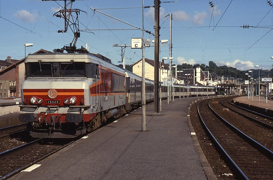 """Another photo from a series of 6 uploaded in February 2012 depicting SNCF electric locos on pasenger trains. With its distinctive maroon, orange and grey livery and Paul Arzens """"Nez Cassé"""" design, an example of class BB15000 is seen at Longuyon. Initially all allocated to Strasbourg depot, they were commonplace on passenger trains in Eastern France. Nowadays with the introduction of TGVs the work has thinned out their use but can still be found in Northern France.  On 3 September 1989, BB15025 was in charge of a train on the once important """"La Transversale Nord-Est"""" route from Lille via Charleville-Mézières to Thionville. Long distance trains such the above from Calais through to Basel would take this route, albeit slow with several reversals have now gone in a system full of TGVs."""