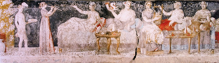 A banquet scene from a Macedonian tomb of Agios Athanasios, Thessaloniki, 4th century BC; shown are six men reclining on couches, with food arranged on nearby tables, a male servant in attendance, and female musicians providing entertainment. Banquet, tombe d'Agios Athanasios.jpg