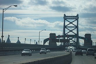 Benjamin Franklin Bridge - The westbound approach to the bridge shows the zipper barrier and the overhead gantry lights